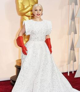 Lady Gaga arrived to Sunday's Academy Awards wearing a white Azzedine Alaïa gown paired with shiny red gloves
